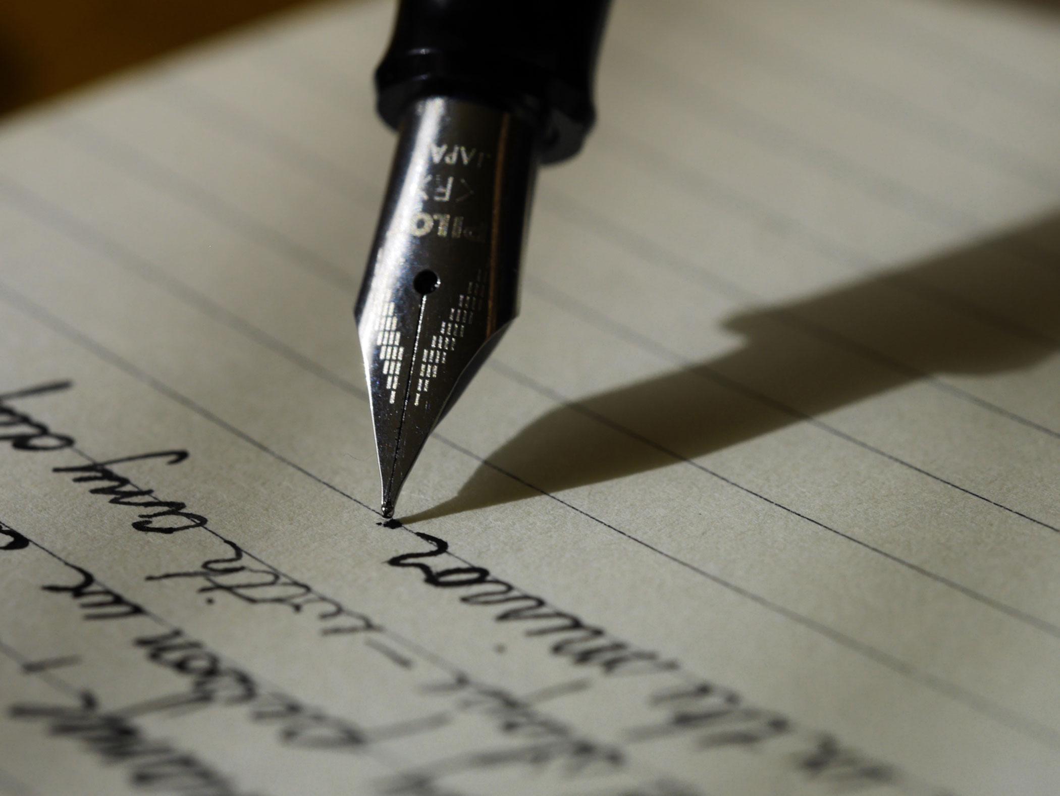 pluma escribiendo papel